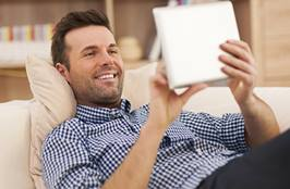 Happy man relaxing on sofa with digital tablet
