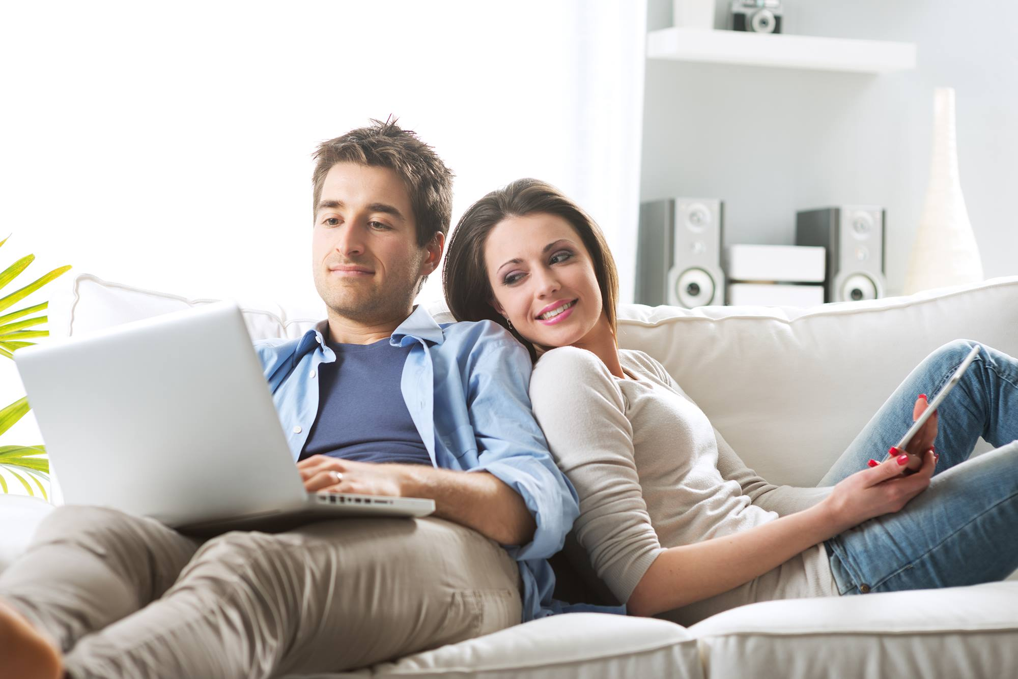 Young couple relaxing on sofa with digital tablet and laptop.